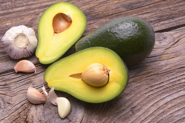 Wall Mural - Avocado and garlic on wooden background