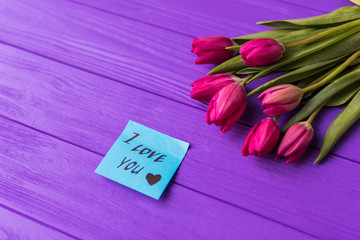 Pink colorful tulips over a purple background, in a flat lay composition and inscription on paper i love you.