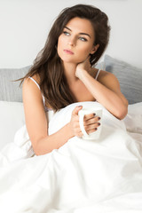 Sick woman sitting under a blanket