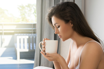 Beautiful woman drinking coffee or tea in bedroom