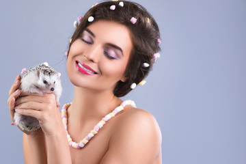 Beautiful woman is holding a cute little hedgehog
