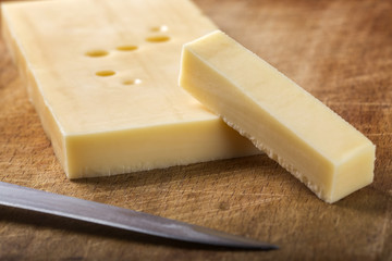 Emmental cheese with knife on wood