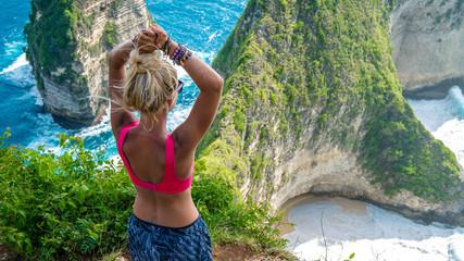 Girl raising her hands on Cliff at Manta Bay or Kelingking Beach, Nusa Penida Island, Bali, Indonesia