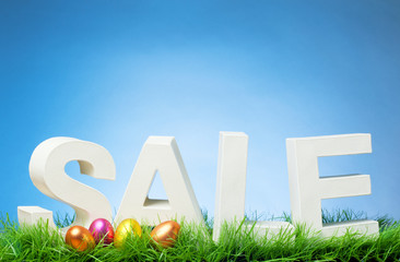 Easter Sale - Word on Grass and Eggs with Blue Sky and Copy Space