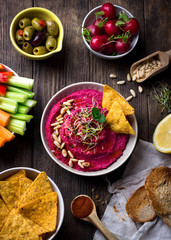 Homemade roasted beet root hummus served with variety of snacks; Overhead view