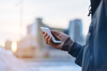 Man using smart phone outdoor with city on the background, Close up of male hand holding phone, blurred background, shallow DOF