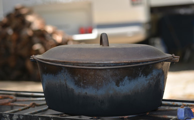 Cast Iron Dutch Oven In Front of Wood Pile
