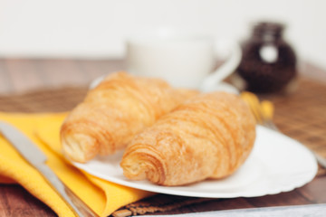 Wall Murals Coffee beans two croissants on a plate, yellow napkin