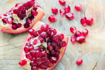 two pieces of red pomegranate on the wooden background