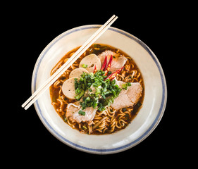 Bowl of noodles with vegetables and pig isolate on black background