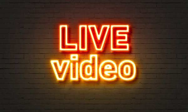 Live video neon sign on brick wall background.