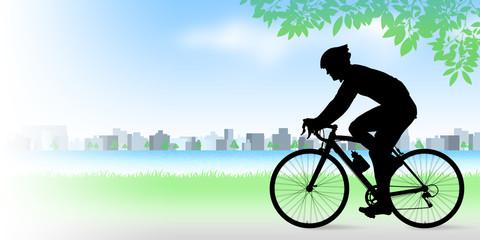 河原でロードバイクに乗る男性