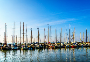 Sail boats moored in the small harbor of the historic fishing village of Marken in the Netherlands under clear skies