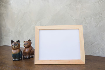 photo Frame and toy cat on a wooden on Gray wall background .
