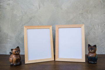 Two photo Frame and toy cat on a wooden on Gray wall background .