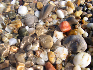 Background from colorful sea pebbles, water and foam.
