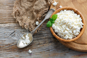 Wooden bowl with fresh cottage cheese.