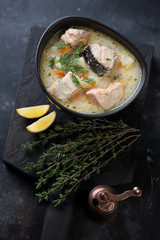 Bowl of finnish fish soup on a dark wooden serving board