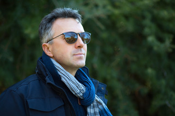 Handsome man. Outdoor winter male portrait. Attractive confident middle-aged man in sunglasses.