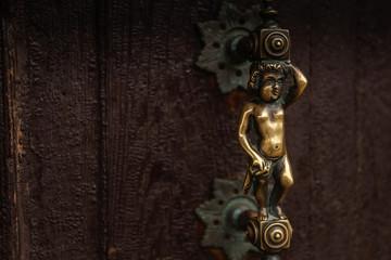 Antique bronze latch on a wooden door in Venice, Italy