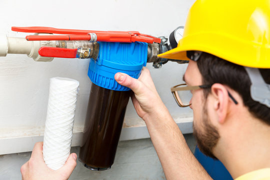 water filtration - plumber changing dirty water filter