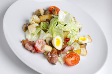 Salad with fried bacon and vegetables on a white plate on a white background