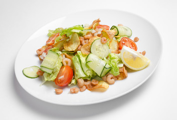 Salad from seafood and vegetables on a white plate