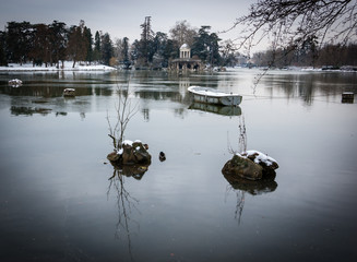 Snow covered boat in the lake and Love Temple at backgrounds.  Lake Daumesnil (Vincennes forest, Paris, France). Vignette.