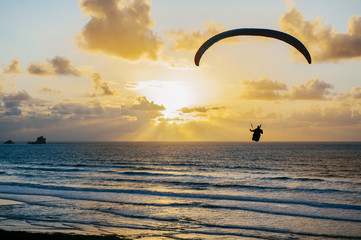 Silhouette of person flying on the parachute over the sea in sunset lights.