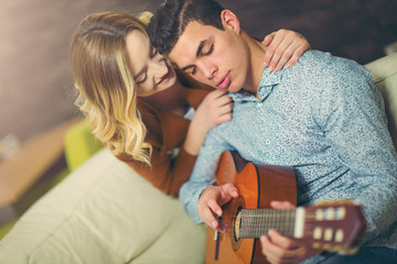 Young and attractive couple sitting near the couch with a guitar. The male is playing the guitar. Selective focus