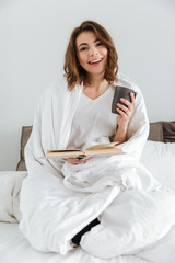 Lady sitting on bed while reading book and drinking coffee.