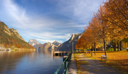 View of a bank of Ebensee lake with a maple alley in autumnal time, Austria