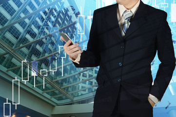 Double exposure of businessman holding smart phone with growth graph chart and blurred building background.
