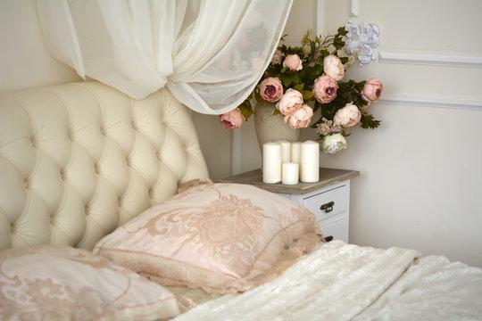 Ваза с цветами, свечи стоят на тумбочке рядом с кроватью в спальне