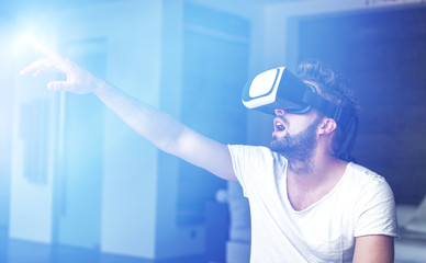 Young man with VR glasses playing virtual reality with blue glowing light source