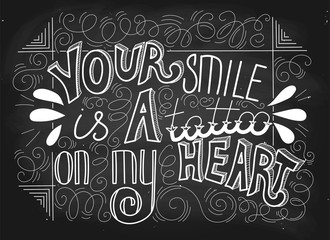 Your smile is a tattoo on my heart. Hand drawn lettering white text on a blackboard background, vector. Can be used for print on cards, t-shirts, dish, posters