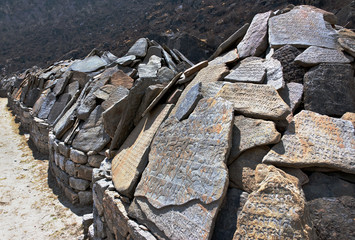Ancient stones carved with the buddhist mantras near great stupa in Khumjung - Nepal, Himalayas