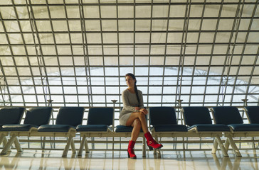 Beautiful young woman is sitting on the bench in an airport and waiting a flight