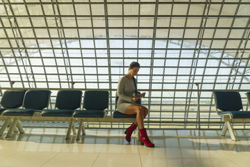 Beautiful young woman is sitting on the bench in an airport, waiting a flight and looking at her travel ticket