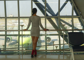 Beautiful young woman stands in the airport, waits a flight and looks at window of travel lounge