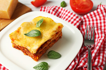 Plate with delicious lasagna and napkin on table