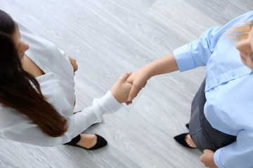 Employer and applicant shaking hands after interview, top view