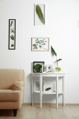 Frames with green leaves in interior on white background