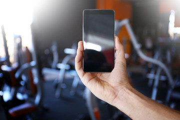 Human hand with mobile phone and blurred gym on background