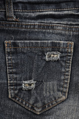 Texture fragment of denim in classic tones with bright seams of thin fabric and a large pocket. The background image on the production of rigid denim clothing