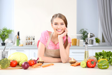 Young woman with different vegetables at kitchen