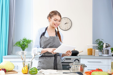 Young woman using tablet for searching recipe in internet