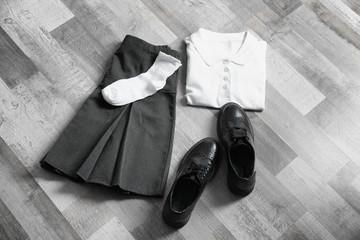 Clothes of schoolgirl on wooden floor, flat lay
