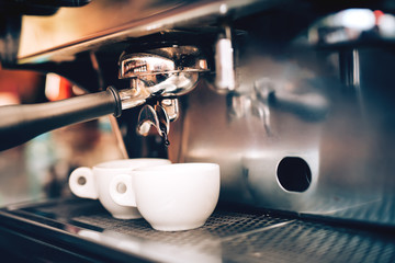 Professional coffee brewing. Espresso machine preparing and pouring two perfect cups of coffee. Restaurant details
