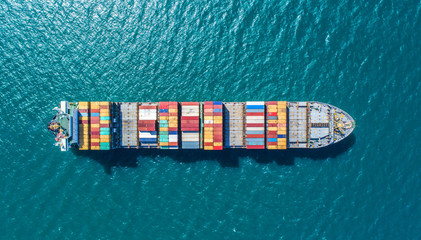 container ship in import export and business logistic.By crane ,Trade Port , Shipping.cargo to harbor.Aerial view.Water transport.International.Shell Marine.Top view. Fotomurales